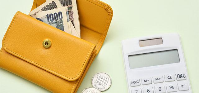 お金が入った財布と電卓