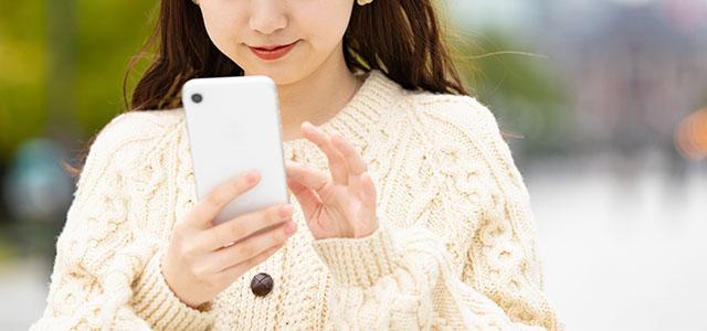 スマホでマッチングアプリを利用する女性